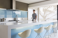 Blurred motion man walking through white and blue modern kitchen - CAIF15528