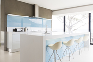 White and clean modern kitchen with stools at kitchen island - CAIF15531