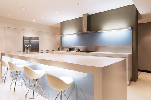 Modern white kitchen with kitchen island and stools illuminated at night - CAIF15546