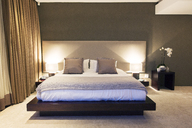 Modern bedroom with double bed illuminated at night - CAIF15549