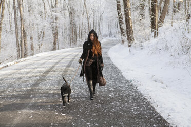 Portrait of young woman walking with dog on road during winter - CAVF06978