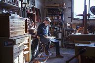 Full length of carpenter reading document in workshop - CAVF06993