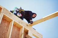 Low angle view of smiling worker making construction frame against clear blue sky - CAVF07005