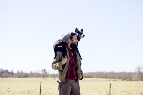 Thoughtful man carrying dog on shoulders while standing at field against clear sky - CAVF07020