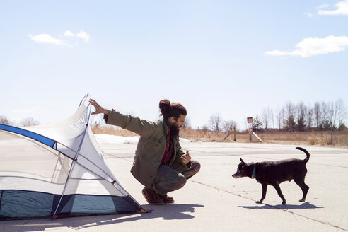 Full length of man holding tent while looking at dog at campsite - CAVF07029