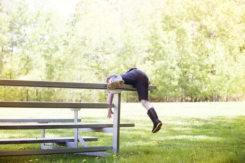 Playful boy climbing on bench at park - CAVF07053