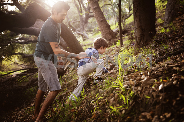 Man assisting son in climbing at forest - CAVF07110