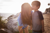 Happy mother kissing son at beach during sunset - CAVF07113