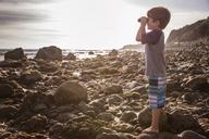 Side view of boy looking through binoculars at beach - CAVF07122
