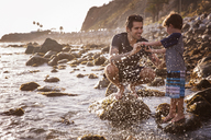Happy father and son enjoying at beach during sunset - CAVF07125