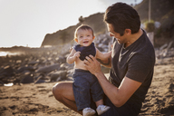 Father with cheerful baby boy at beach - CAVF07134