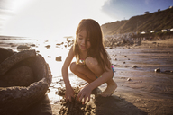 Girl playing in sand at beach during sunset - CAVF07137