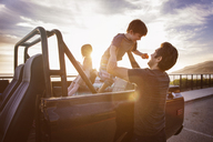 Man lifting boy from pick-up truck during sunset - CAVF07146