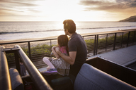 Father and daughter looking at view during sunset - CAVF07149