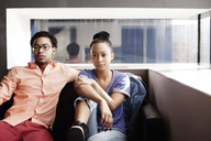 Portrait of couple sitting on sofa at home - CAVF07209