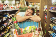 Man sleeping on shopping cart in grocery store - CAIF15552