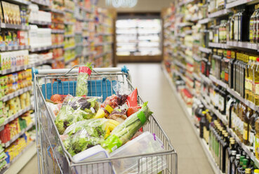 Close up of full shopping cart in grocery store - CAIF15555