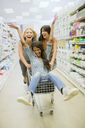 Women playing with shopping cart in grocery store - CAIF15558