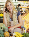 Woman talking on cell phone while shopping in grocery store - CAIF15567