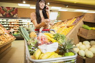 Woman talking on cell phone in grocery store - CAIF15579