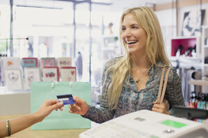 Woman paying with credit card in clothing store - CAIF15582