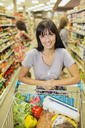 Woman pushing full shopping cart in grocery store - CAIF15585