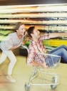 Blurred view of couple playing in grocery store - CAIF15588