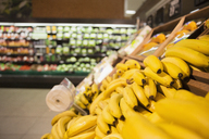 Close up of bananas in produce section of grocery store - CAIF15600