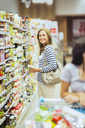 Smiling woman shopping in grocery store - CAIF15606