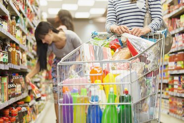 Woman pushing full shopping cart in grocery store - CAIF15612