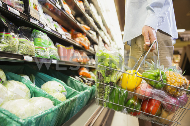 Man carrying full shopping basket in grocery store - CAIF15615
