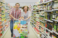 Couple playing with shopping cart in grocery store aisle - CAIF15618