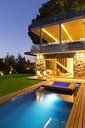 Modern house overlooking illuminated swimming pool at night - CAIF15642