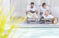Couple relaxing in lawn chairs by swimming pool - CAIF15669
