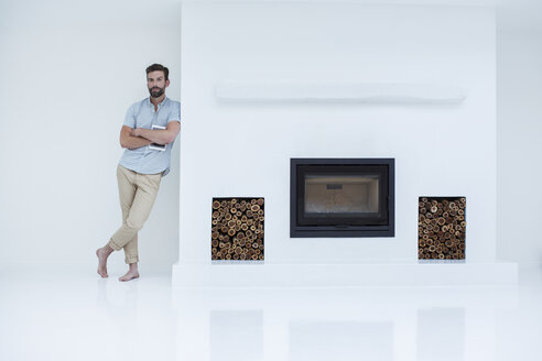Man leaning on modern fireplace - CAIF15678