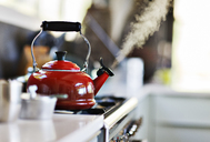 Red old fashion kettle on cooker with steam coming out - CAIF15684