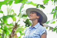 Smiling woman wearing straw hat looking at plants in sunny garden - CAIF15702
