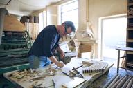 Male carpenter chiseling wood in workshop - CAVF07498
