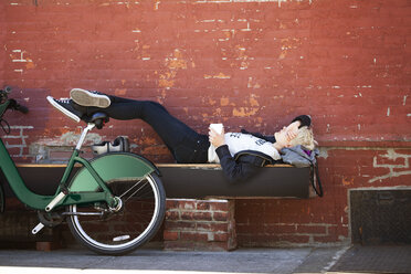 Woman lying on bench by parked bicycle against wall - CAVF07504