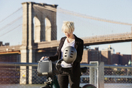 Woman standing with bicycle against Brooklyn Bridge in city - CAVF07525