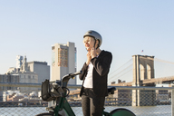 Woman wearing helmet while standing by river in city against clear sky - CAVF07528