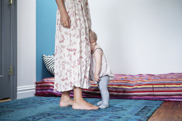 Baby leaning on mother in bedroom - CAVF07534