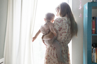 Mother carrying baby by window at home - CAVF07537