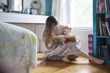 Mother reading book with cheerful baby while sitting on floor - CAVF07540