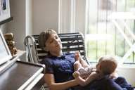 Happy mother sitting with baby girl on lounge chair at home - CAVF07558