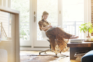 Woman reading book while sitting on chair at home - CAVF07570