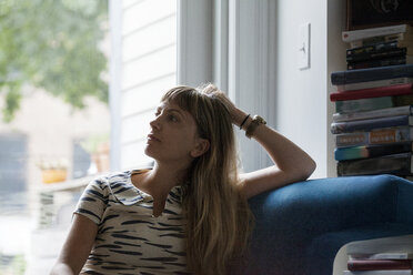 Thoughtful woman sitting on sofa against window at home - CAVF07573