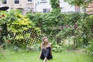 Thoughtful woman sitting on grassy field at backyard - CAVF07576