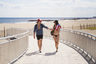 Couple walking on boardwalk at beach during summer vacation - CAVF07609