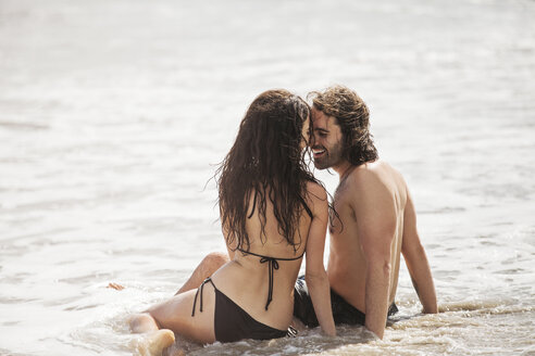 Romantic couple sitting on shore at beach during summer vacation - CAVF07612